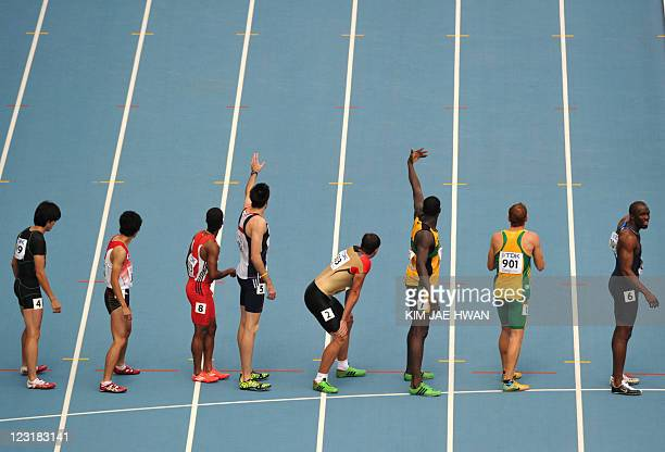 Competitors wait for the baton handover during the men's 4x400 metres relay heats at the International Association of Athletics Federations World...