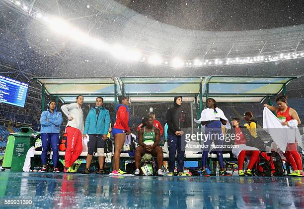Competitors wait under an awning as rain falls at the Olympic Stadium on Day 10 of the Rio 2016 Olympic Games on August 15 2016 in Rio de Janeiro...
