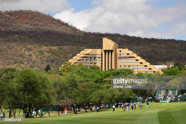 Competitors walk down the first fairway as the Cascades hotel is seen in the background during day one of the Nedbank Golf Challenge at Gary Player...