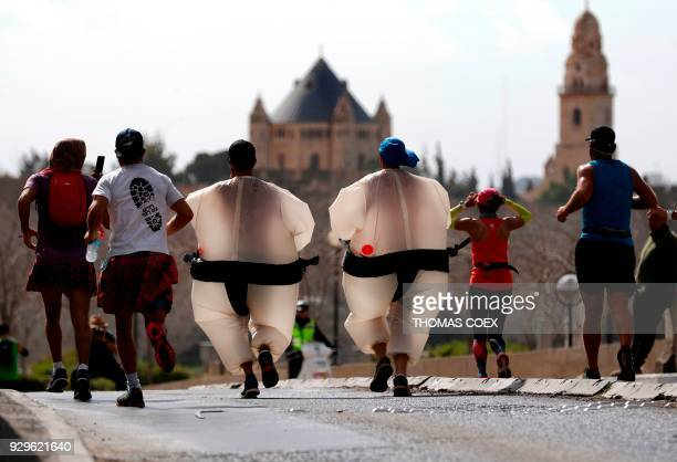 TOPSHOT Competitors with sumo disguises take part in the 8th International Jerusalem marathon with the Church of Dormition on the background on March...