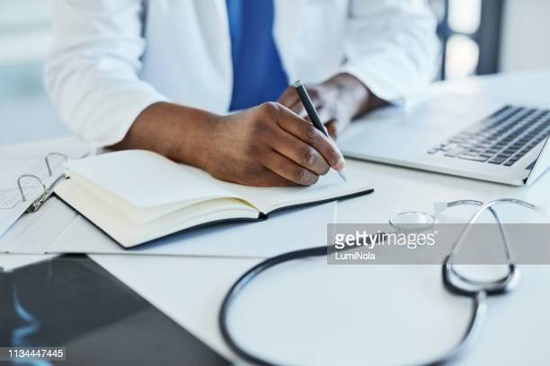 compiling new treatment plans for his patients - medical chart stock pictures, royalty-free photos & images
