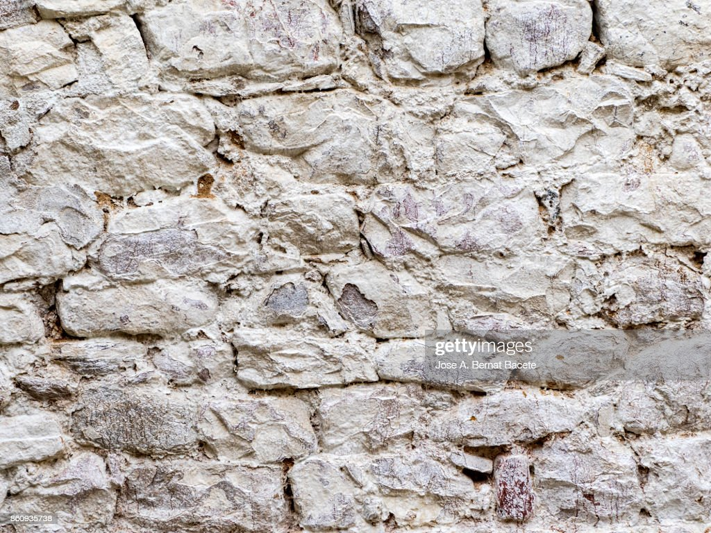 Complete setting of a facade of a cement wall with stones of white colors, ancient and spoil in the time : Stock Photo