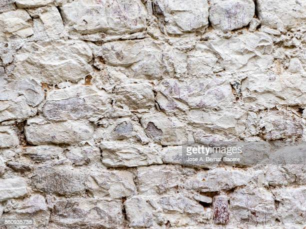 complete setting of a facade of a cement wall with stones of white colors, ancient and spoil in the time - stone wall stock pictures, royalty-free photos & images