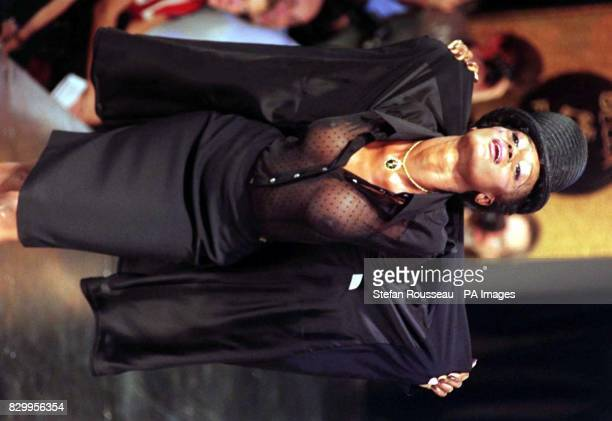 Complete with hat and veil a model wears an elegant black pencil skirt with matching long jacket and chiffon shirt from the latest collection by...