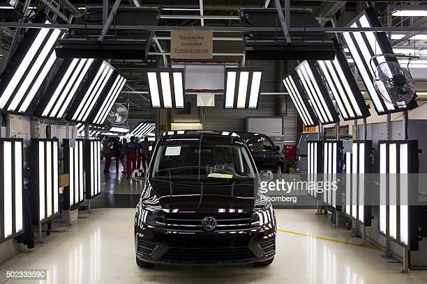 A completed black Volkswagen AG Caddy van sits illuminated in the quality control inspection bay at the end of the production line at the VW plant in...