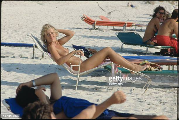 A completely nude sunbather enjoys her time in the sun whil reclining in a