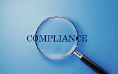 Compliance Concept - Magnifier And Compliance Text On Blue Background