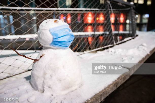 Compliant snowman with a medical facemask as seen in the night after the first snowfall of the year in Eindhoven city center in the Netherlands on 16...