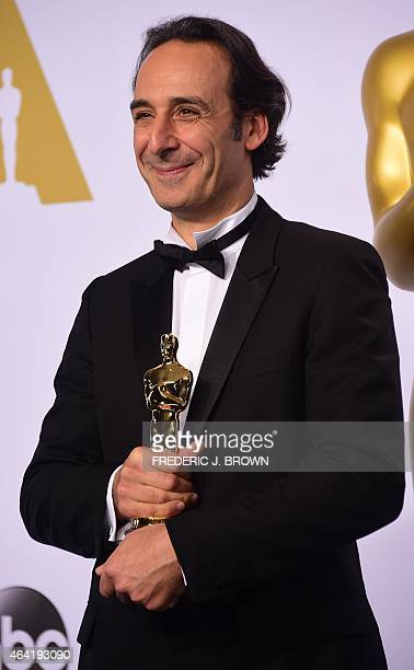 Composer Alexandre Desplat poses with his Oscar for Best Original Score for The Grand Budapest Hotel in the press room during the 87th Oscars on...
