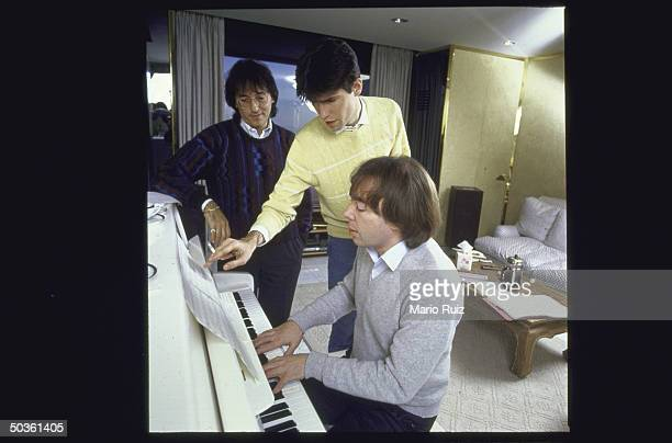 Composer Andrew LLoyd Webber playing piano while working on his new show with lyricists Don Black and Charles Hart