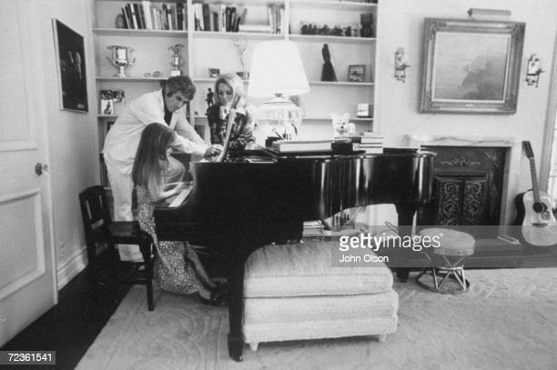 Composer Burt Bacharach Jr and his actress wife Angie Dickinson watching their daughter play the piano