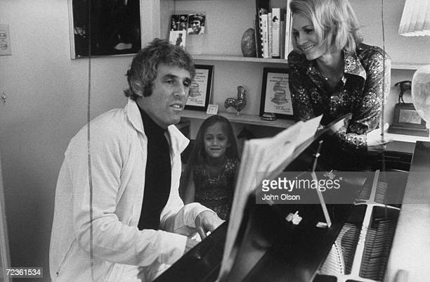 Composer Burt Bacharach Jr playing the piano while his actress wife Angie Dickinson and daughter watch and listen