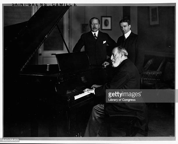 Composer Camille SaintSaens plays the piano while two men look on