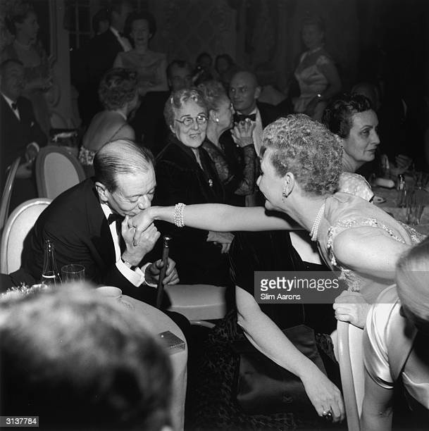 Composer Cole Porter kisses the hand of actress Mary Martin at a party to celebrate the 5th anniversary of the show 'South Pacific'