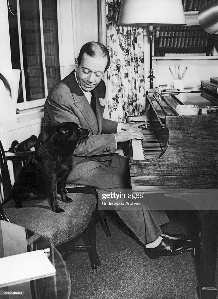Composer Cole Porter playing the piano with his dog on a chair beside him, circa 1956.