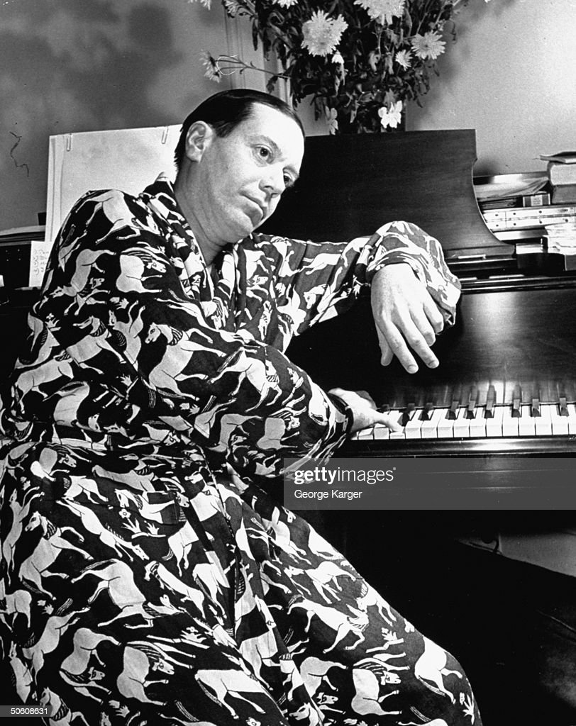 Composer Cole Porter sporting robe w. wild horse print as he noodles on piano while staying in the Ritz Hotel during out-of-town tryouts for his new Broadway-bound musical Du Barry Was a Lady.