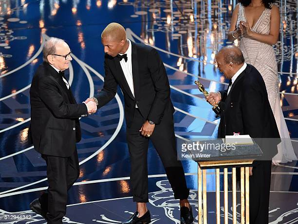 Composer Ennio Morricone accepts the Best Original Score award for ''The Hateful Eight' from musicians Pharrell Williams and Quincy Jones onstage...