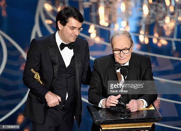Composer Ennio Morricone accepts the Best Original Score award for 'The Hateful Eight' onstage with Italian interpreter during the 88th Annual...
