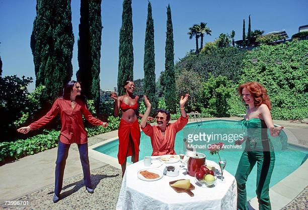 Composer producer and musician Georgio Moroder eats breakfast at home by his pool while backup singers dance around him in April 1979 in Los Angeles...
