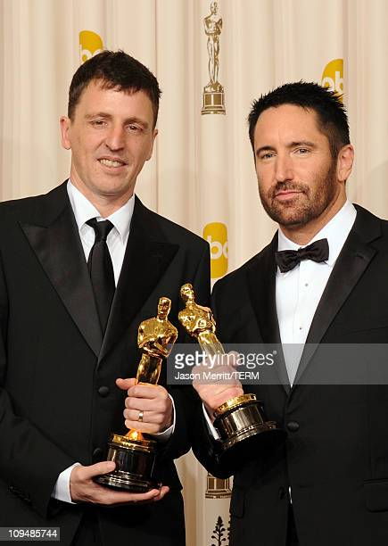 Composers Atticus Ross and Trent Reznor winners of the award for Best Original Score for 'The Social Network' pose in the press room during the 83rd...