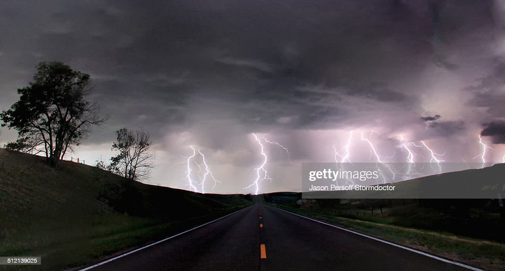 A composite image from 5 images of cloud-to-ground lightening bolts at the end of a rural road, Lexington, Nebraska, USA : Stock Photo