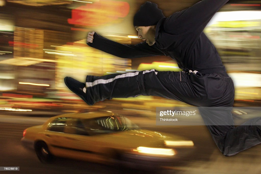 Composite image of a man leaping over a fast moving taxi cab : Stock Photo