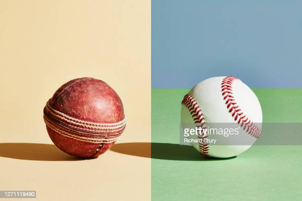 composite image of an old cricket ball and new baseball ball - richard drury stock pictures, royalty-free photos & images