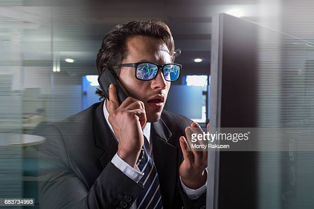 Composite image of businessman on phone at computer screen with graphical data reflected in glasses