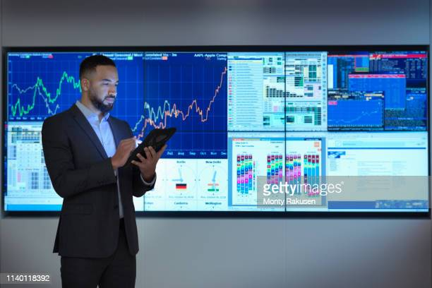 composite image of businessman using digital tablet in front of digital charts - scrutiny stock pictures, royalty-free photos & images