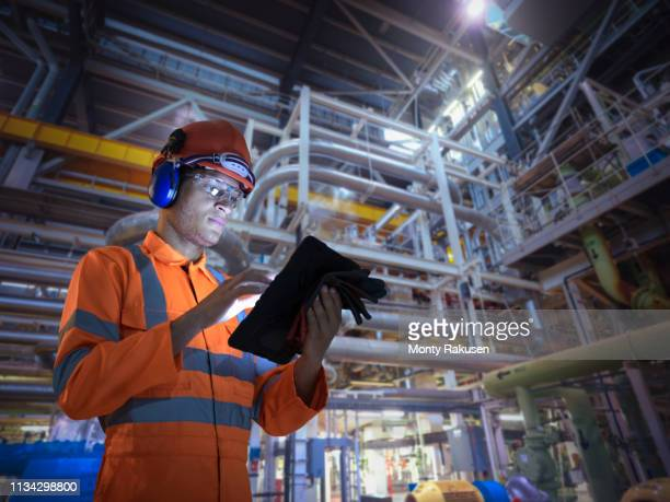 composite image of engineer in nuclear power station using digital tablet - nuclear power station stock pictures, royalty-free photos & images