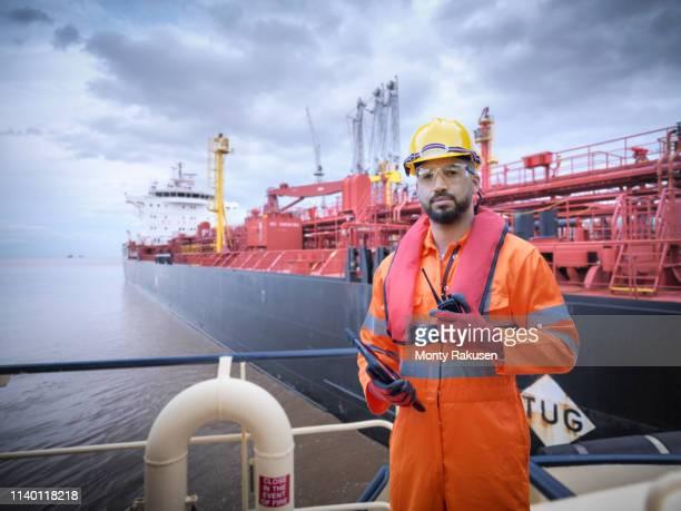 composite image of ship worker on tugboat with oil tanker - marine engineering stock pictures, royalty-free photos & images