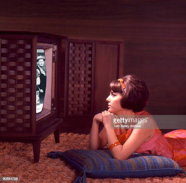 Composite image shows a young woman in a pink and orange dress lies on the floor and watches an episode of 'The Honeymooners' on a console television...