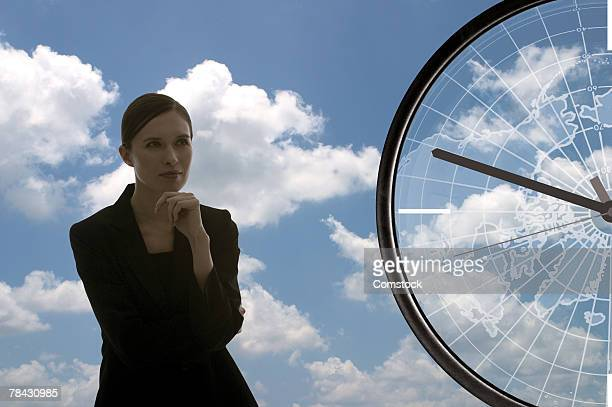 Composite of businesswoman and compass in sky