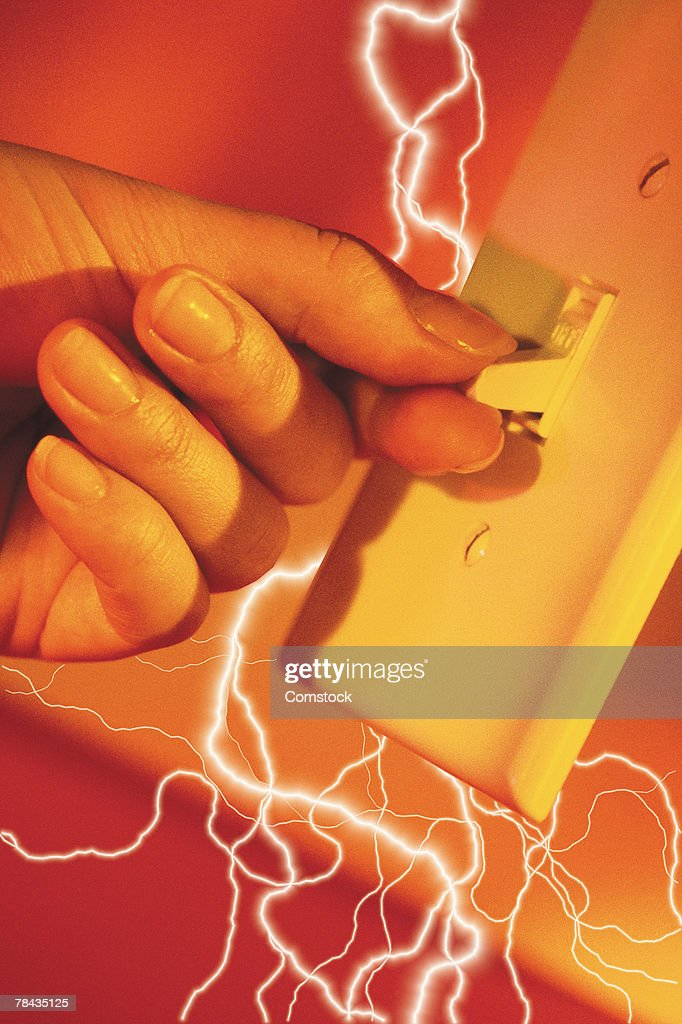 Composite of lightning bolts and fingers flicking a light switch on : Stockfoto
