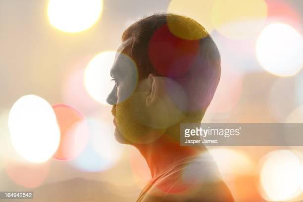 composite of mans head and blurred lights - licht natuurlijk fenomeen stockfoto's en -beelden
