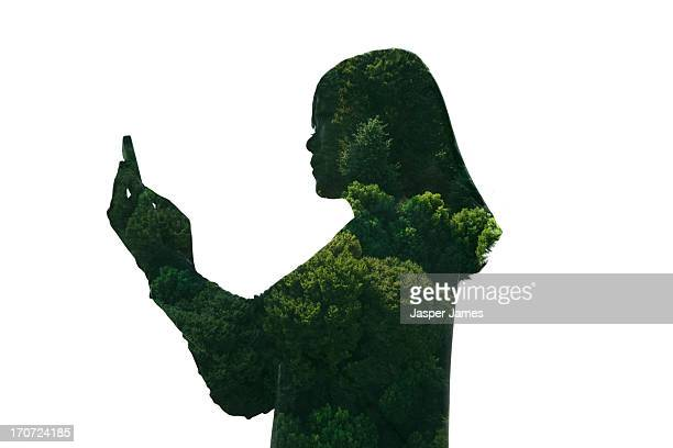 composite of woman texting on phone and green tree
