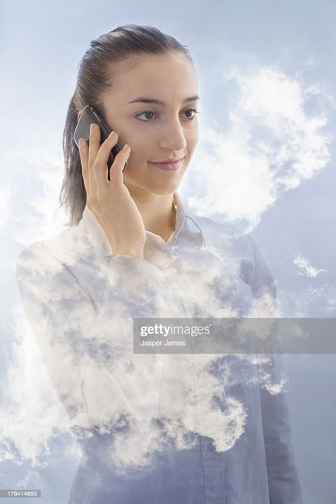 composite of woman using mobile phone and blue sky : Stock Photo