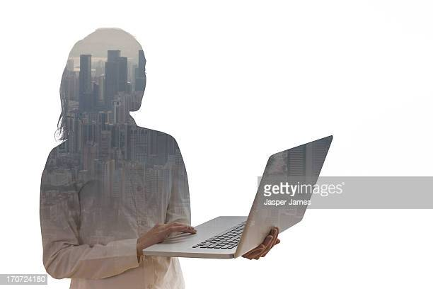 composite of young woman using a laptop and citysc
