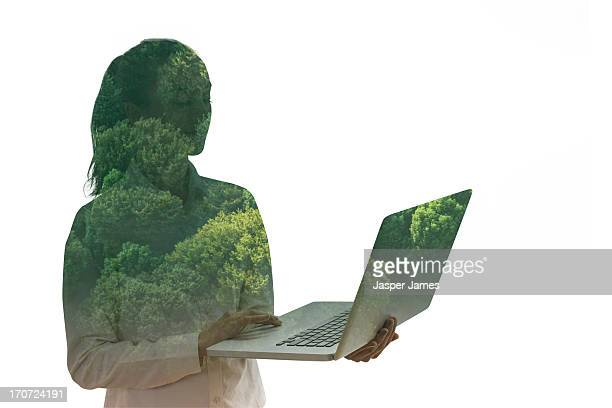 composite of young woman using laptop and trees