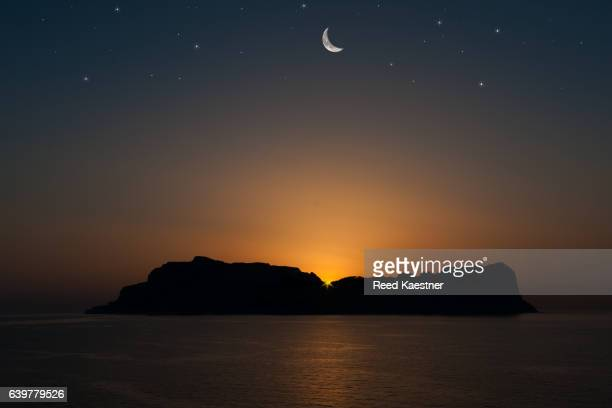 A composited image of Capri at twilight with a cresent moon and stars.