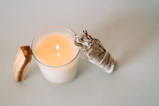 Composition made of Palo Santo stick, burning candle and White Sage on gray background. Set for aromatherapy and rituals. Top view and macro