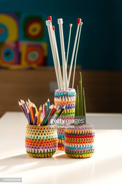 composition of three crochet vases with pencils, knitting needles and a plant - pencil case stock pictures, royalty-free photos & images