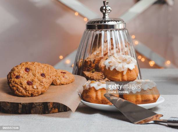 composition on the table with cup of coffee and three cupcake in glaze light background - shell game stock photos and pictures