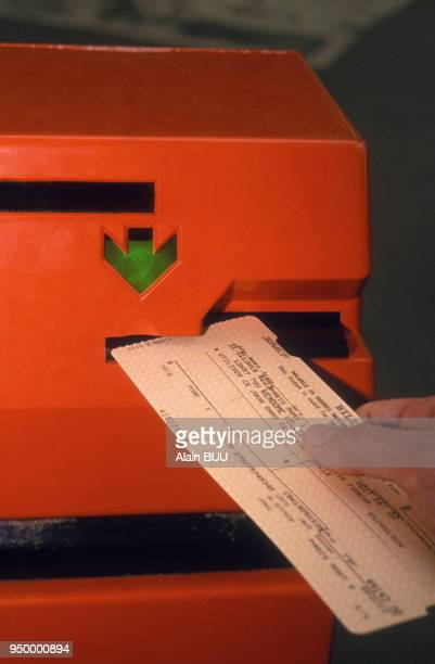 Compostage d'un titre de transport SNCF au moment du depart en train le 12 Janvier 1993 à Paris France