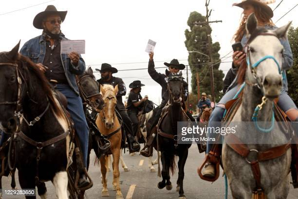 Compton Cowboys, some lifting their ballots, ride through the streets of Compton towards the Compton Library to cast their votes in a ballot box on...