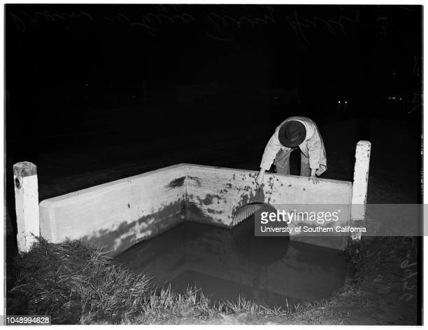 Compton drowning 18 January 1952 Reporter pointing to drain where Terry Hall 3 years was drowned 'Sleeve reads A9456'Compton California USA