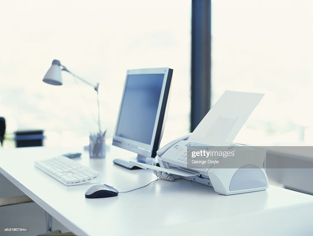 computer and a fax machine on a desk in an office stock photo
