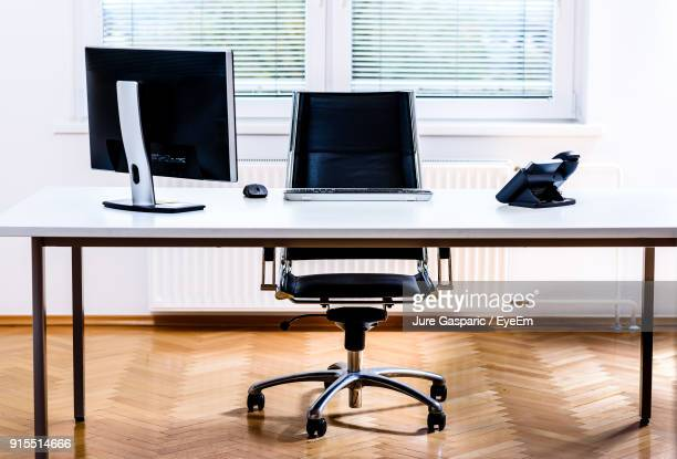 computer and landline phone on desk in office - office chair stock pictures, royalty-free photos & images
