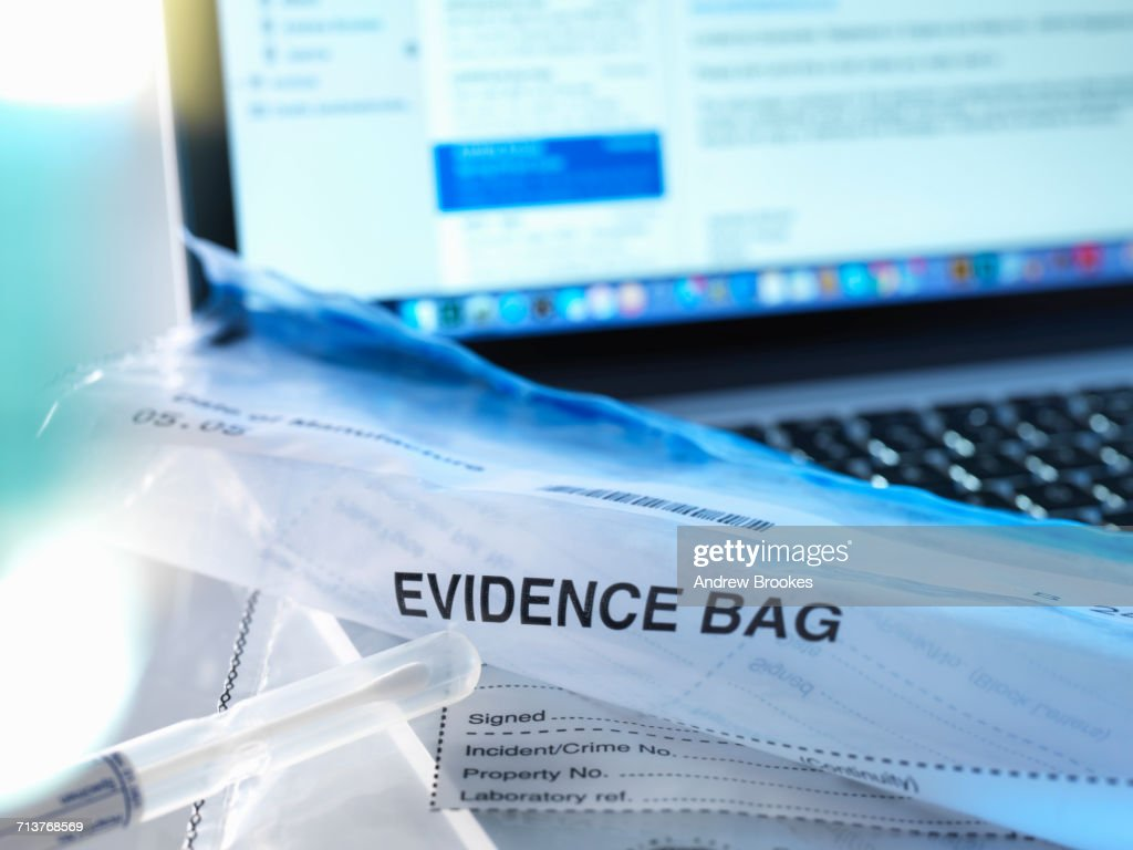 Computer crime, evidence being taken from a laptop computer : Stock Photo