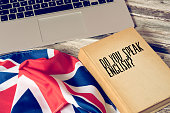 A computer, flag of Great Britain and book titled Speak English
